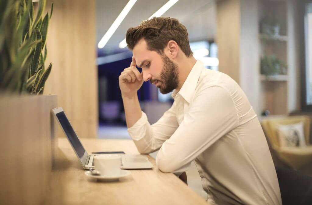 betenkt mann ved laptop