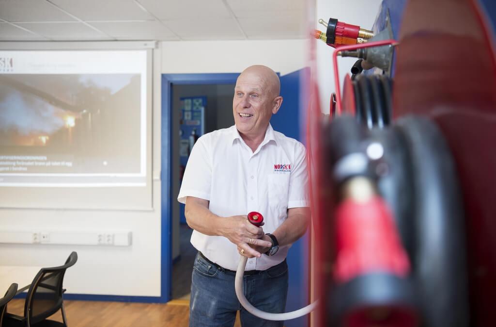 Trond B. Hansen ved brannslange